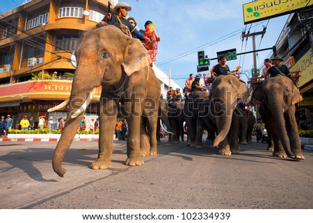 Surin, Isan, Thailand - November 19, 2010: Herd of elephants and riding tourist passengers marching in downtown during the annual Surin Elephant Roundup parade #102334939