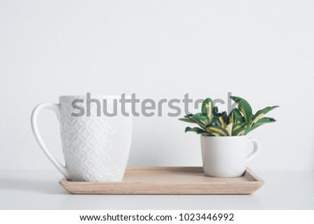 Bamboo tray with white coffee mug and yellow-green leaves  #1023446992