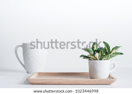 Bamboo tray with white coffee mug and yellow-green leaves  #1023446998