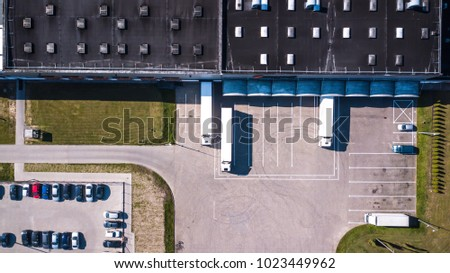 Aerial view of goods warehouse. Logistics center in industrial city zone from above. Aerial view of trucks loading at logistic center #1023449962
