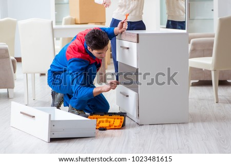 Contractor repairman assembling furniture under woman supervision #1023481615