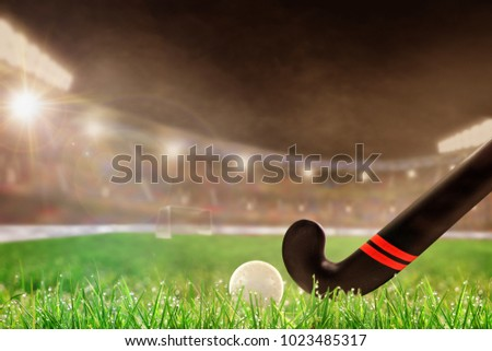 Field hockey stick and ball on grass in brightly lit outdoor stadium with focus on foreground and shallow depth of field on background. Deliberate lens flare and copy space.