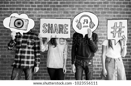 Friends holding up thought bubbles with social media concept icons #1023556111
