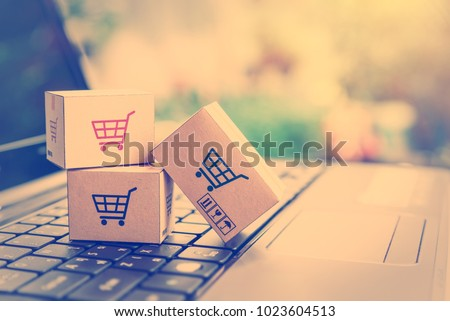 Online shopping / ecommerce and delivery service concept : Paper cartons with a shopping cart or trolley logo on a laptop keyboard, depicts customers order things from retailer sites via the internet. #1023604513