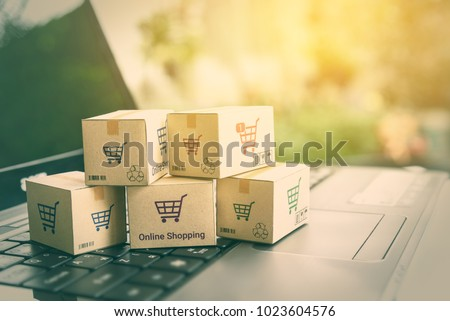 Online shopping / ecommerce and delivery service concept : Paper cartons with a shopping cart or trolley logo on a laptop keyboard, depicts customers order things from retailer sites via the internet. #1023604576