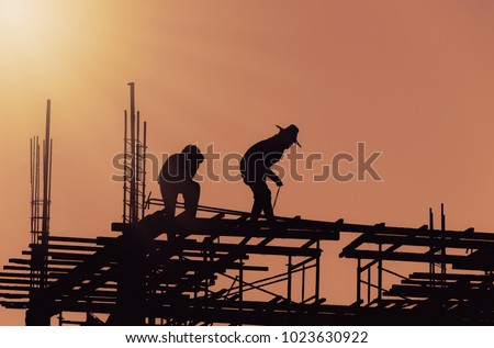 Silhouette City worker, construction crews to work on high ground heavy industry and safety concept over blurred natural background sunset  #1023630922