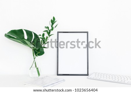 Desk with photo frame, notebook, computer, green leaves. Creative workspace. Front view, copy space, mock up