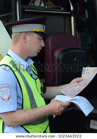 MOSCOW REGION, RUSSIA - AUGUST 3,2017:The inspector of the road police patrol checks documents from the driver of the intercity passenger bus. #1023663922