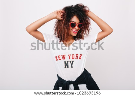Indoor photo of excited girl with light-brown skin and curly hair dancing with charming smile. Portrait of blissful young woman in glasses posing with hands up on white background. #1023693196