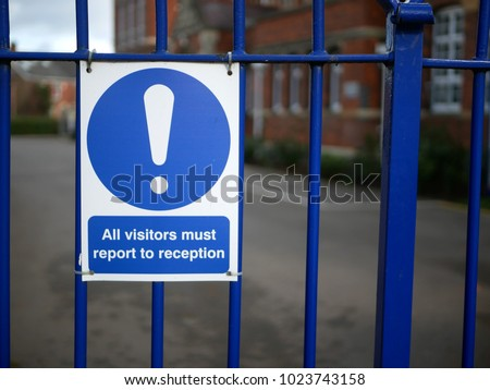 Concept of school security or stranger danger shown by visitors must report to reception sign on blue fence in front of British girls secondary grammar school