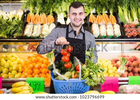 Young man seller helping to buy fruit and vegetables in grocery shop #1023796699