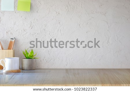 Front view of wood desk with coffee mug and house plant. workspace and copy space Royalty-Free Stock Photo #1023822337
