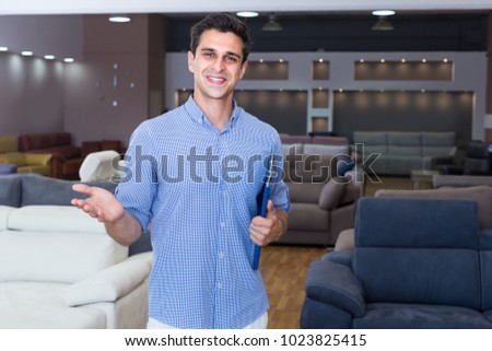 Seller man is showing prices on sofas in store. #1023825415
