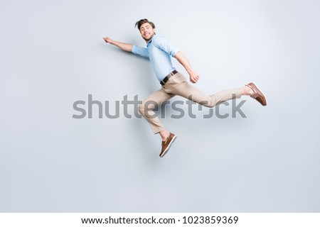 Happy, attractive, handsome, young man with bristle jumping in air showing superman pose looking at camera with beaming smile over grey background #1023859369