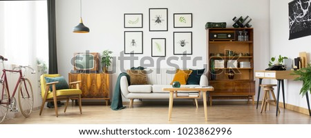 Retro living room design with old television, cabinet and radio along with work area with typewriter Royalty-Free Stock Photo #1023862996
