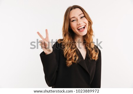 Picture of happy woman 20s with long auburn hair in black jacket posing on camera and showing peace or victory sign isolated over white background