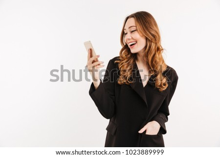 Image of sociable curly woman in black jacket smiling and looking on her smartphone holding in hand isolated over white background