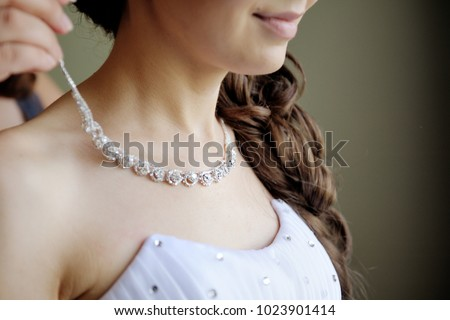 Morning gathering of the bride. Women's hands fasten a necklace on the neck of the bride. Closeup. #1023901414