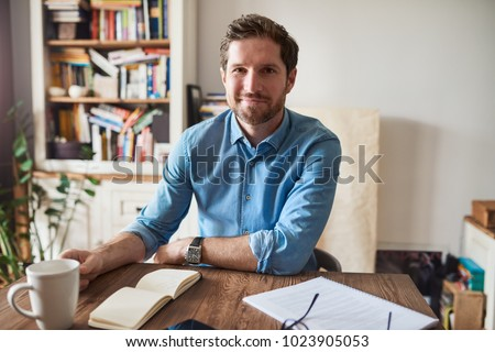Smiling young man sitting at a table in his living room writing down notes in a notepad while working from home #1023905053