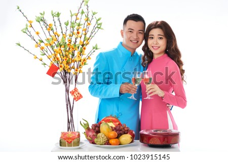 Portrait of cheerful Vietnamese young couple drinking champagne at New Year celebration #1023915145