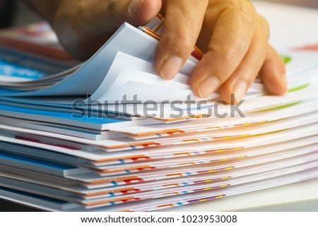 Businessman hands searching unfinished documents stacks of paper files on office desk for report papers, piles of sheet achieves with clips on table, Document is written, drawn,presented. #1023953008