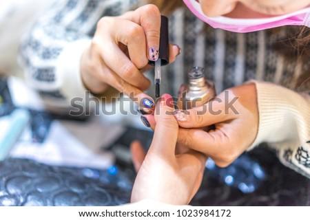 woman paints nails #1023984172