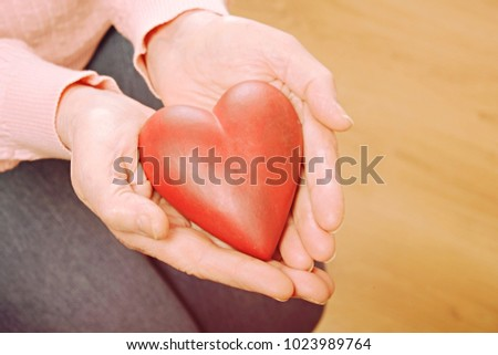 Elderly woman holds heart in her arms. Senior old female lady, sister of mercy holding love symbol in wrinkled hands. Heart disease prevention prophylaxis concept. Mother's day, close up, background. #1023989764