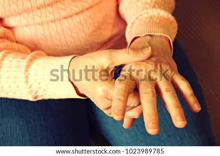Elderly woman applying moisturizing lotion cream on hand palm, easing aches. Senior old lady experiencing severe arthritis rheumatics pains, massaging, warming up arm. Close up, copy space, background #1023989785