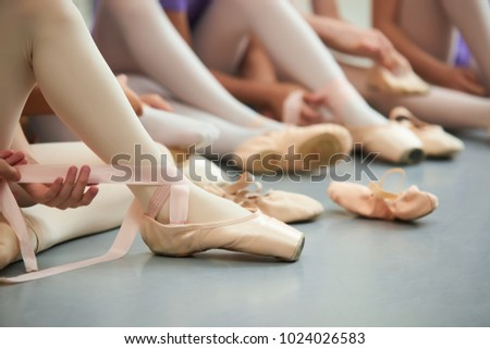 Ballet dancer tying ballet shoes. Close up ballet girl putting on her pointe shoes sitting on the floor, blurred background. #1024026583