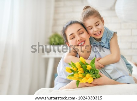 Happy women's day! Child daughter is congratulating mom and giving her flowers tulips. Mum and girl smiling and hugging. Family holiday and togetherness. #1024030315