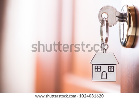 House key on a house shaped silver keyring in the lock of a entrance  brown door #1024031620