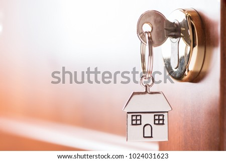 House key on a house shaped silver keyring in the lock of a entrance  brown door #1024031623