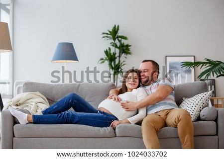 Image of happy future parents sitting on gray sofa #1024033702