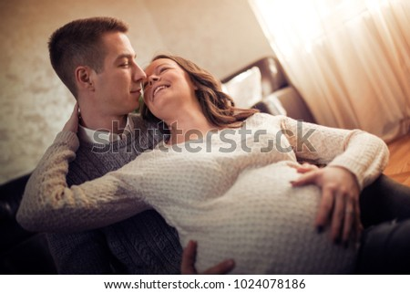Happy man touching belly of smiling pregnant woman in their home. #1024078186