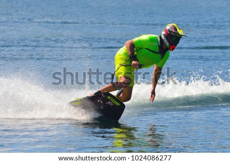 WYBOSTON, BEDFORDSHIRE, ENGLAND - JULY 08, 2017: Male Motosurf Competitor Taking corner at speed creating a lot of spray. #1024086277