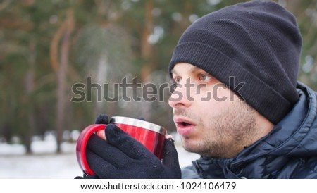 Portrait of cheerful attractive young man drinking hot tea outdoors in winter #1024106479