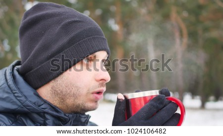 Young man drinking tea or coffee in forest. Traveler man in forest in winter time. Man traveler hands holding cup of tea. #1024106482