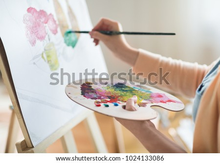 art, creativity and people concept - close up of artist with palette and brush painting still life on paper at studio