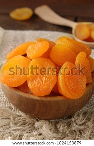 Dried apricots in a bowl on a wooden background. #1024153879