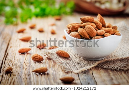 Almonds in white porcelain bowl on wooden table. Almond concept with copyspace. #1024212172