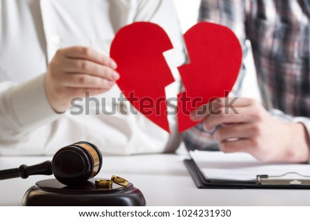 Hands of wife, husband signing decree of divorce, dissolution, canceling marriage, legal separation documents, filing divorce papers or premarital agreement prepared by lawyer. Wedding ring #1024231930