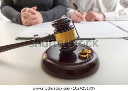 Hands of wife, husband signing decree of divorce, dissolution, canceling marriage, legal separation documents, filing divorce papers or premarital agreement prepared by lawyer. Wedding ring #1024231939