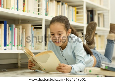 Pretty little happy Asian girl lying on the floor at the library or bookstore enjoying reading a book smiling cheerfully copyspace leisure weekend holidays education children family kids store shop #1024249501