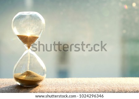 Life time passing concept. Hourglass with sun light background Royalty-Free Stock Photo #1024296346