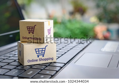 Online shopping / ecommerce and delivery service concept : Paper cartons with a shopping cart or trolley logo on a laptop keyboard, depicts customers order things from retailer sites via the internet. #1024344034