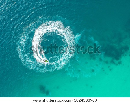 People are playing a jet ski in the sea.Aerial view. Top view.amazing nature background.The color of the water and beautifully bright. Fresh freedom. Adventure day.clear turquoise at tropical beach #1024388980