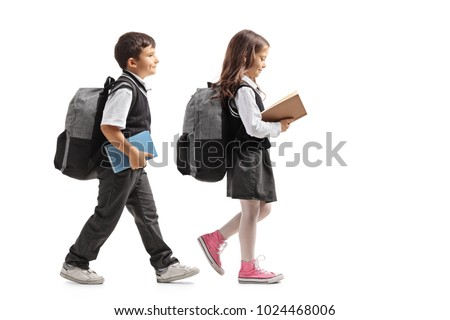 Full length profile shot a schoolboy and a schoolgirl with backpacks and books walking isolated on white background #1024468006