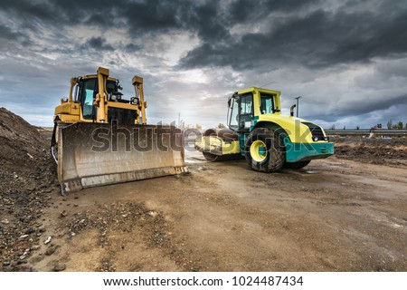 Excavator performing earthmoving work on construction sites of a road #1024487434