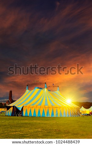 Nonamed circus tent under a warn sunset and chaotic sky without the name of the circus company which is cloned out and replaced by the metallic structure #1024488439