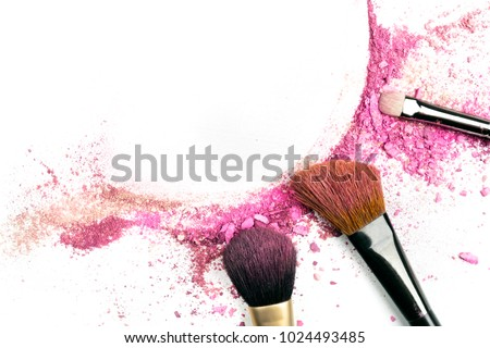 Traces of vibrant pink powder and blush forming a frame, with makeup brushes and a place for text. A template for a makeup artist's business card or flyer design, with copy space